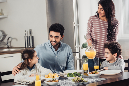 cheerful latin mother holding jar with orange juice near son while looking at husband hugging daughter during lunch Stock Photo
