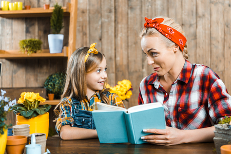 cheerful mother looking at cute daughter while holding book