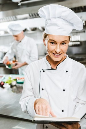 beautiful female chef in uniform holding recipe book and looking at camera in restaurant kitchen Stock Photo