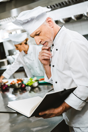 handsome thoughtful male chef propping chin with hand while reading recipe book in restaurant kitchen Stock Photo