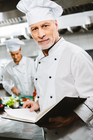 male chef in uniform and hat looking at camera and holding recipe book in restaurant kitchen