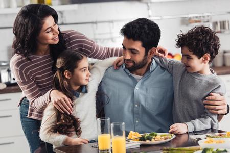 vrolijke Spaanse familie die lacht terwijl ze knuffelt in de buurt van de lunch thuis Stockfoto