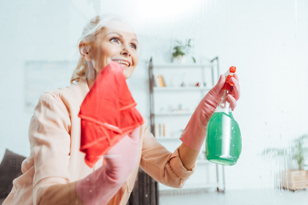 Inspired senior woman cleaning window with spray and rag Stock Photo