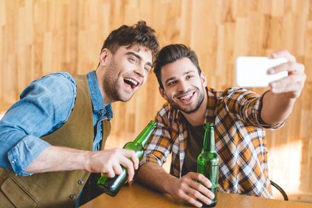 handsome men holding glass bottles of beer and taking selfie