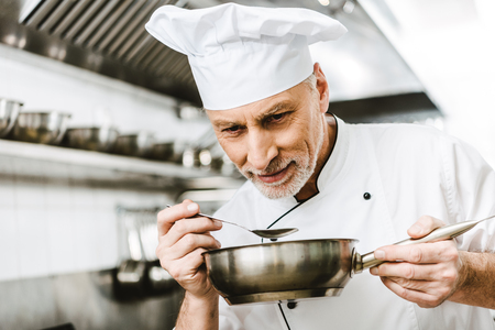 selective focus of handsome male chef in uniform sniffing dish in pan in restaurant kitchen Stockfoto