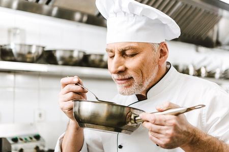 handsome male chef in uniform sniffing dish in pan in restaurant kitchen Imagens