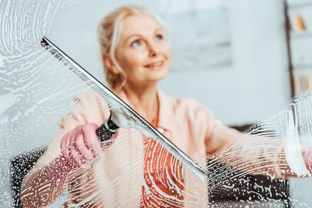 Smiling senior woman cleaning window with glass wiper Stock Photo