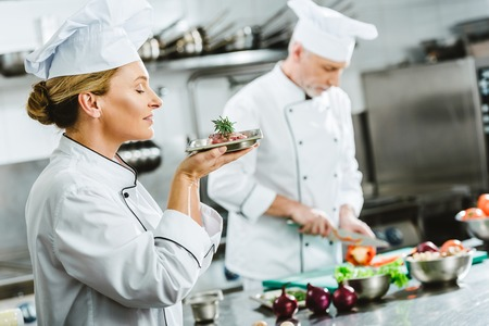 female chef in uniform holding meat dish on plate with male colleague cooking on background in restaurant kitchen
