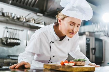 beautiful female chef in uniform enjoying aroma of meat steak on wooden board in restaurant kitchen Stockfoto