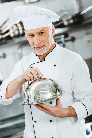 handsome male chef in uniform looking at camera and holding serving tray with dome in restaurant kitchen