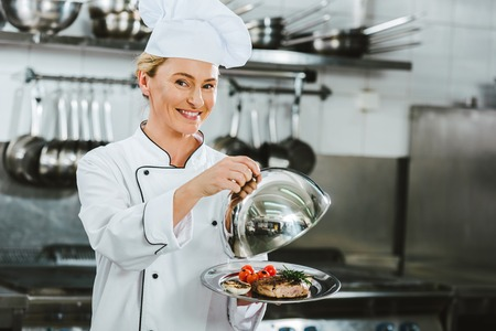 beautiful smiling female chef in uniform holding dome from serving tray with meat dish in restaurant kitchen