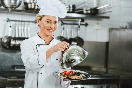 Hermosa mujer chef sonriente en uniforme sosteniendo la cúpula de la bandeja de servir con plato de carne en la cocina del restaurante