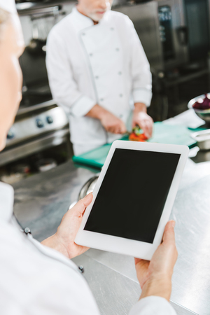 partial view of female chef using digital tablet with blank screen in restaurant kitchen