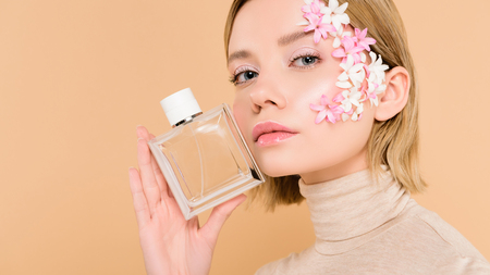 confident woman with flowers on face holding bottle of perfume isolated on beige 版權商用圖片