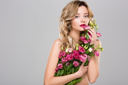 Bella mujer posando con ramo de flores de primavera Eustoma aislado en gris