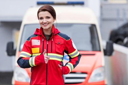 Charmante Sanitäterin in roter Uniform zeigt Daumen nach oben