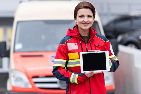 Smiling paramedic in red uniform holding digital tablet with blank screen