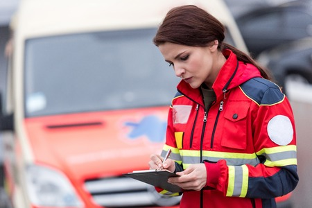 Konzentrierte Sanitäterin in Uniform in der Zwischenablage schreiben