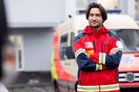 Paramédico confiado en uniforme rojo de pie en la calle con los brazos cruzados.