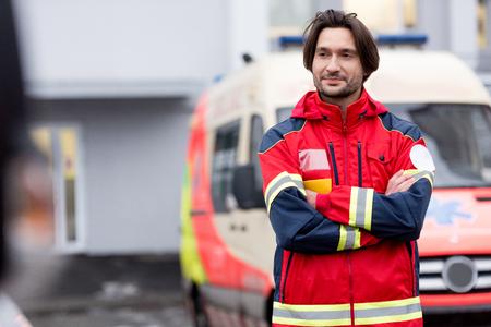 Selbstbewusster Sanitäter in roter Uniform, der mit verschränkten Armen auf der Straße steht