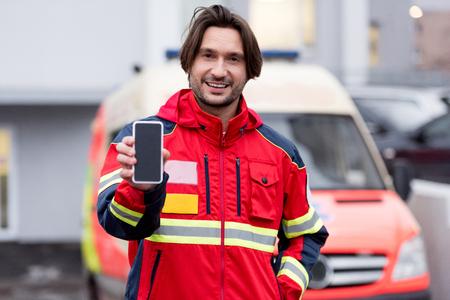 Paramédico sonriente en uniforme rojo con smartphone con pantalla en blanco