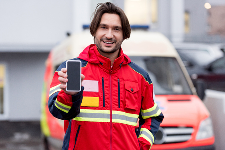 Smiling paramedic in red uniform holding smartphone with blank screen Stock fotó