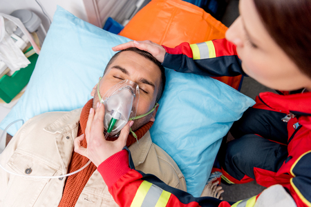 Cropped view of paramedic holding oxygen mask on unconscious patient Stock Photo