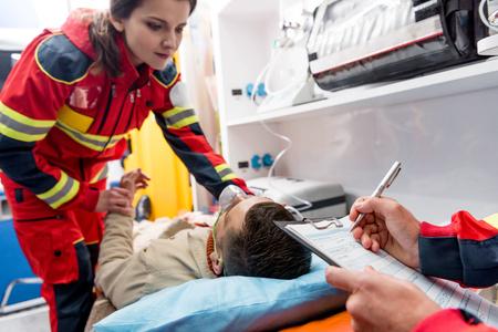 Ausgeschnittene Ansicht des Sanitäters, der eine Diagnose schreibt, während ein Kollege den Puls überprüft Standard-Bild
