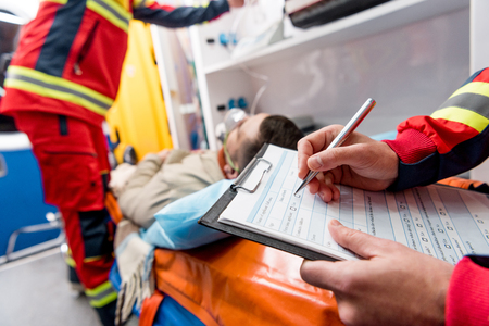 Partial view of paramedic writing diagnosis in clipboard