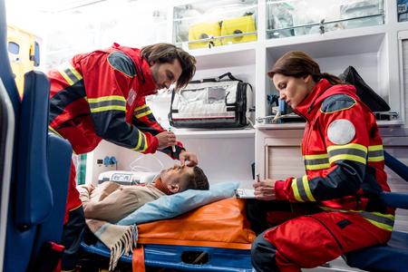 Paramedics doing eye examining in ambulance car