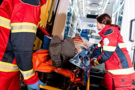 Sanitäter transportieren Patienten auf einer Trage im Krankenwagen Standard-Bild