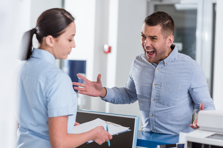 Uomo aggressivo che urla all'infermiera in clinica