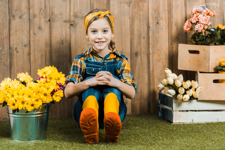 cheerful kid sitting on grass in yellow shoes near flowers Stockfoto - 119588495