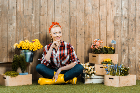 beautiful woman sitting with crossed legs near flowers in wooden boxes