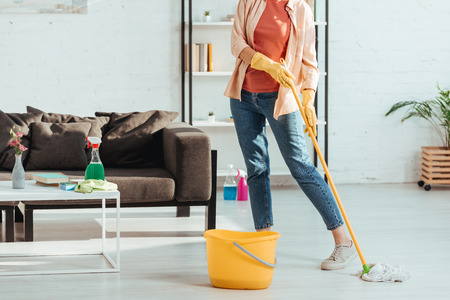 Cropped view of woman in jeans cleaning floor with mop 写真素材