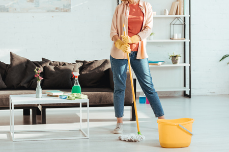 Cropped view of woman cleaning house with mop and bucket