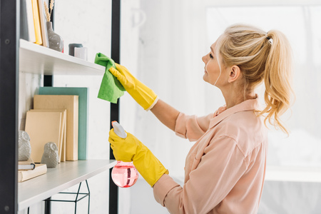 Senior woman with pony tail cleaning shelves with rag