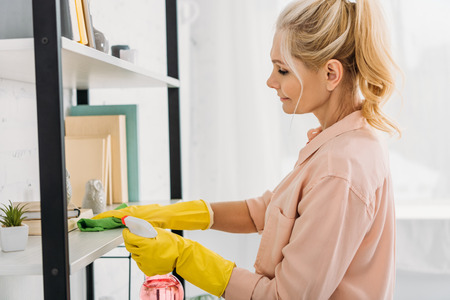 Woman in yellow rubber gloves cleaning shelves with rag and spray