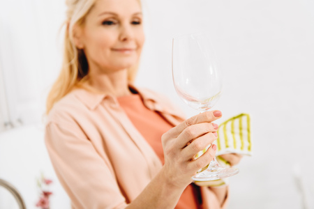 Pleased senior woman wiping wineglass with dishcloth Stockfoto