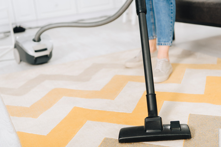 Partial view of woman cleaning striped carpet with vacuum cleaner