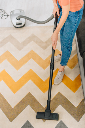 Cropped view of woman in jeans cleaning carpet with vacuum cleaner
