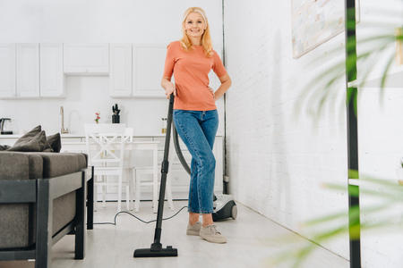 Happy senior woman in jeans cleaning house with vacuum cleaner Stock Photo