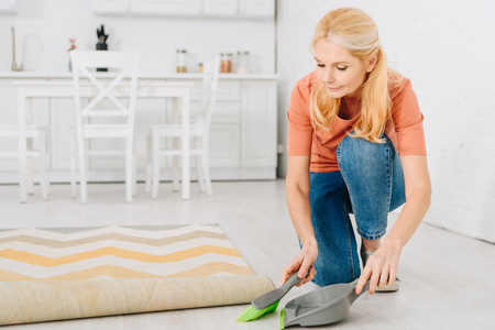 Concentrated woman cleaning floor with brush and scoop