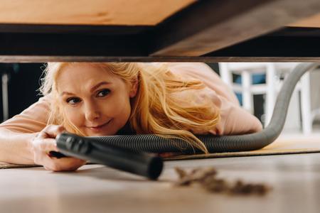 Smiling senior woman using vacuum cleaner under furniture