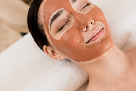 beautiful asian woman lying with clay mask on face at spa Stock Photo