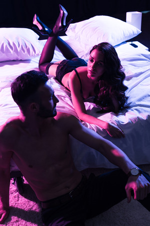 passionate man looking at woman in sexy underwear lying on bed isolated on black Zdjęcie Seryjne