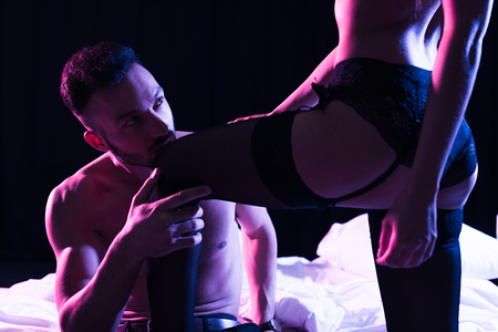 półnagi mężczyzna całujący nogę dziewczyny stojącej w bieliźnie przy łóżku odizolowany na czarno