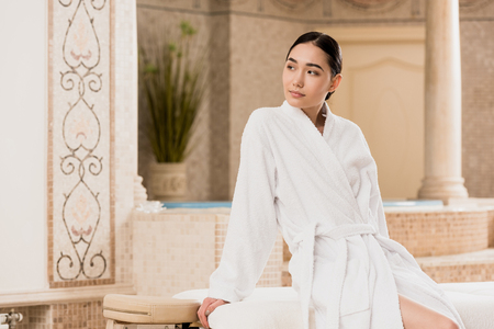 beautiful asian woman in bathrobe sitting and looking away at spa Stok Fotoğraf