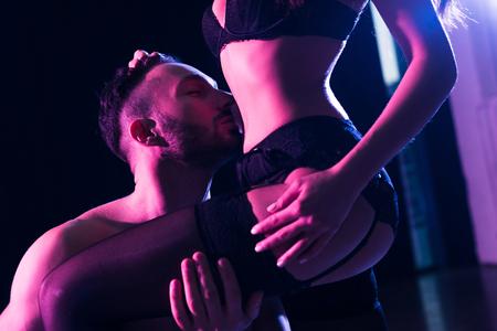 homme passionné embrassant le corps de la petite amie debout en sous-vêtements isolé sur noir Banque d'images