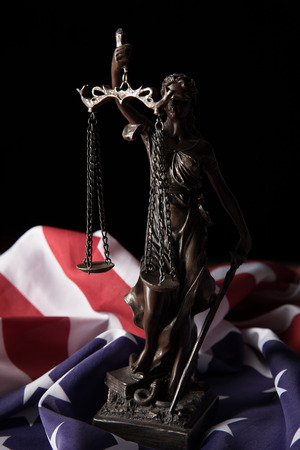 bronze statuette with scales of justice and american flag isolated on black